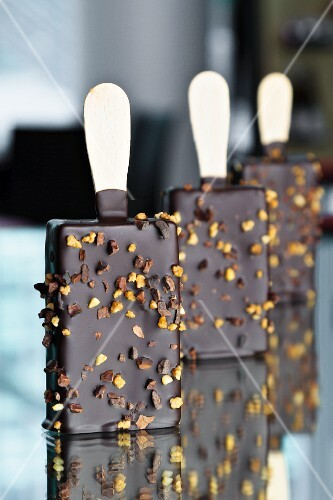 Chocolate ice cream on sticks with chopped nuts