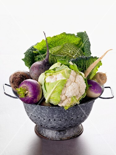 Various types of cabbage and turnips in a colander