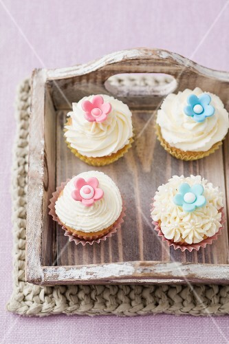 Four cupcakes on a wooden tray