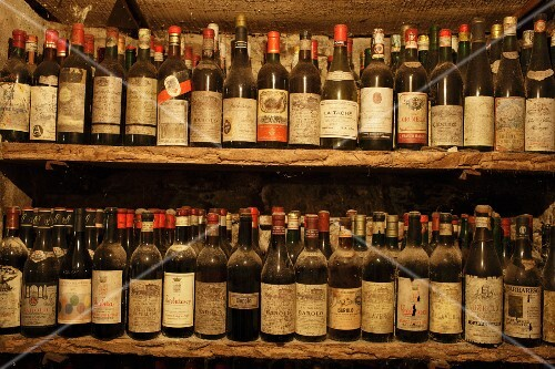 Dusty wine bottles on old shelving