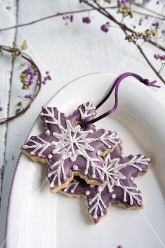 Snowflake-shaped biscuits decorated with purple icing sugar