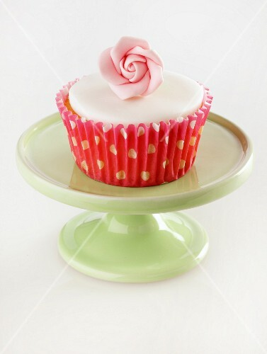 A cupcakes decorated with a sugar rose