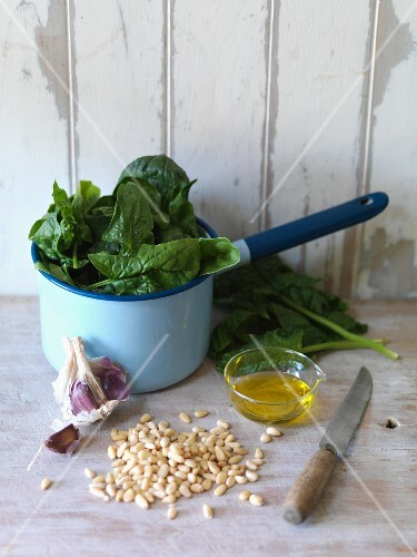 An arrangement of spinach, pine nuts, garlic and oil