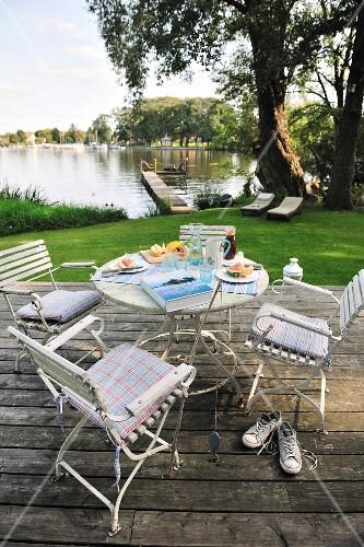 essplatz auf der terrasse weisse st hle und tisch auf holzdeck mit blick auf den weiher bild. Black Bedroom Furniture Sets. Home Design Ideas