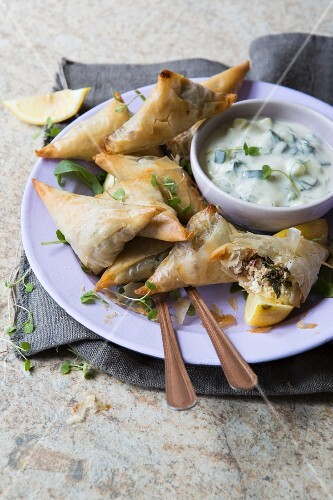 Spanakopitas filled with rocket, walnuts and goat's cheese served with lemon and dill tzatziki
