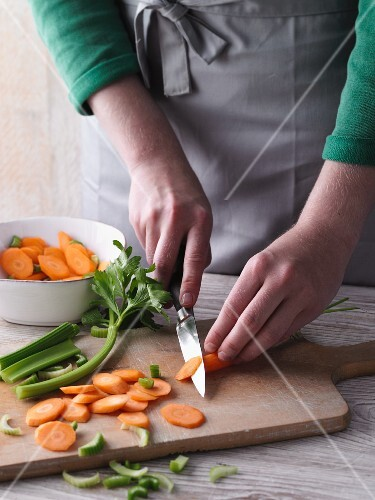 A woman chopping carrots and celery on a chopping board