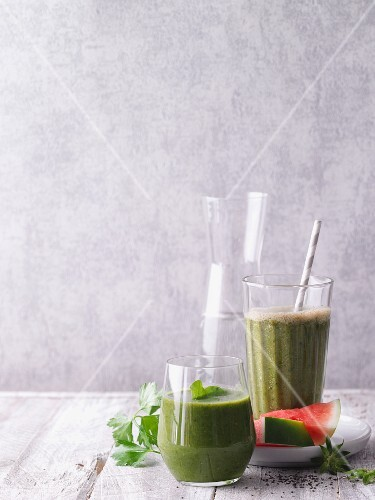 Two green smoothies garnished with lamb's lettuce and watermelon