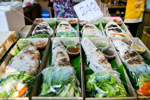 Fish in a salt crust with salad and sauce at a market in Thailand