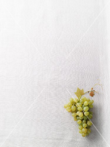 Green grapes on a white surface