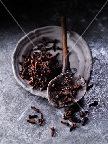 Cloves on a vintage wooden spoon and on a plate
