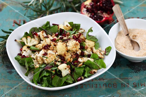 Spinach salad with roasted cauliflower and pomegranate seeds