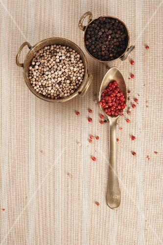 Black, white and pink pepper peppercorns in a bowl and on a spoon