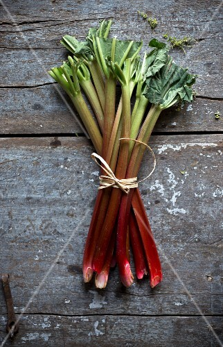 A bundle of rhubarb on a rustic wooden board