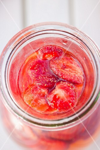 Freeze-dried strawberries and vinegar in a bottle (seen from above)