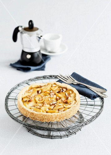 Shortcrust apple cake with slivered almond on a cake stand
