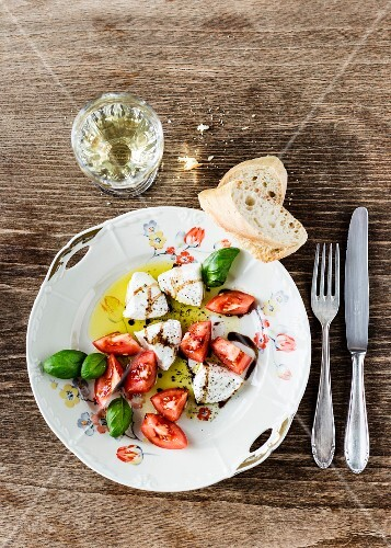 Mozzarella, tomato pieces, basil and bagette with olive oil and balsamic vinegar, old floral-patterned porcelain plate