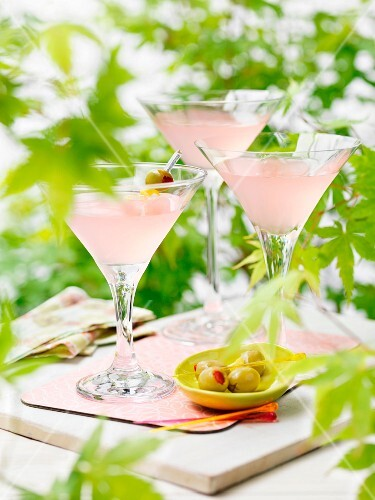 Three martinis with pink grapefruit juice and olives