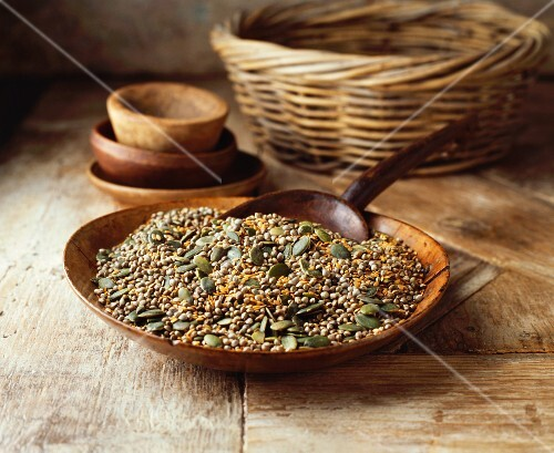Pumpkin seeds, flaxseed and hemp seeds in a wooden bowl on a wooden table