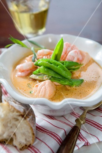 Soup with salmon, prawns and mange tout
