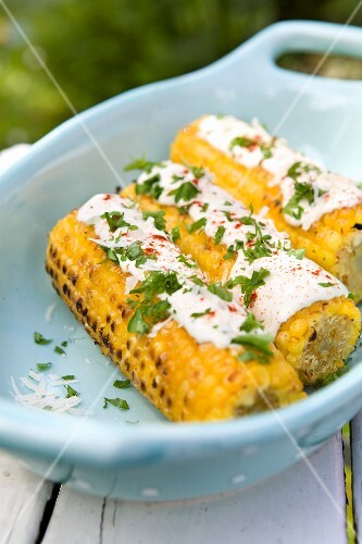 Grilled corn cobs with sauce and parsley