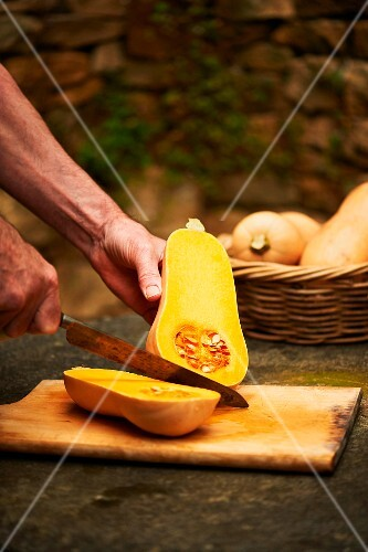A man halving a butternut squash on a wooden chopping board
