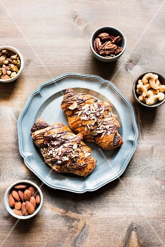Two chocolate croissants on a plate next to various bowls of nuts