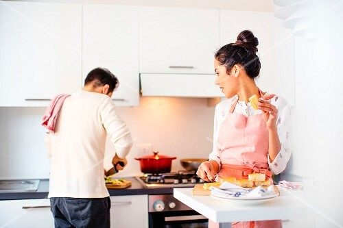 A young couple cooking together in a kitchen