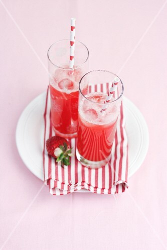 Two glasses of raspberry lemonade with straws