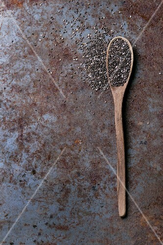 Chia seeds on a wooden spoon on a rusty metal surface (seen from above)