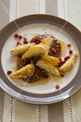 Matcha and banana pancakes with sesame and pomegranate seeds