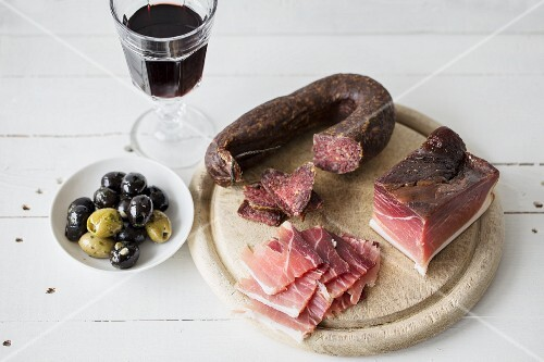 Ham and salami with olives and red wine
