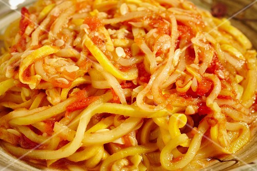 Cooked yellow squash pasta served with tomato sauce