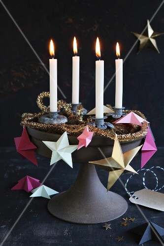 A unique Advent wreath on a cake stand decorated with paper stars, a golden garland and four burning candles