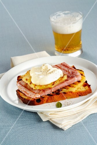 A slice of grilled panettone topped with pineapple, ham and sour cream