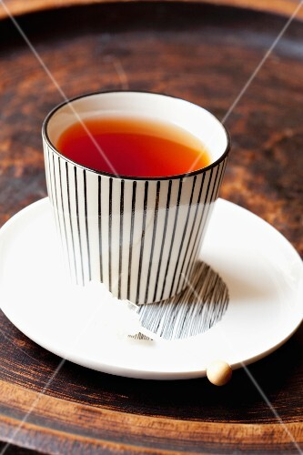 A cup of rooibos tea with a rock sugar stick