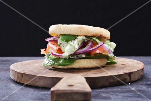 Fish burger with salmon and spinach on a wooden board (Sweden)