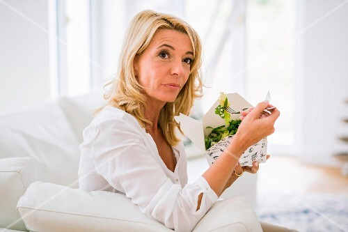 A blonde middle-aged woman sitting on a sofa eating vegetables from a takeaway box