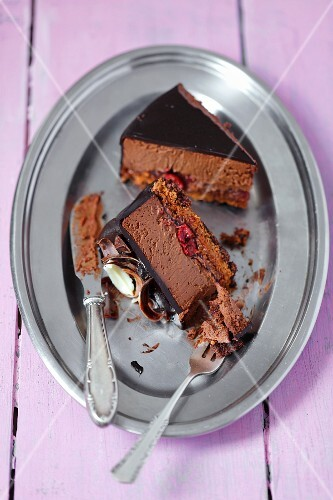 Two slices of chocolate cake with cherries