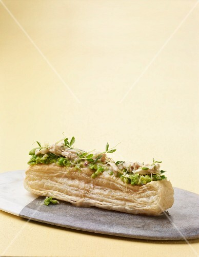 A puff pastry slice with pea cream, crab meat, horseradish and pea sprouts