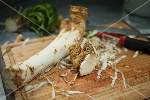 A peeled horseradish root on a wooden chopping board