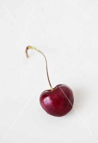 A cherry on a white surface