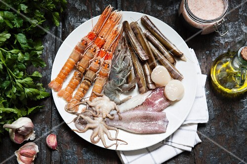 Various types of seafood on a plate with olive oil, herbs and garlic