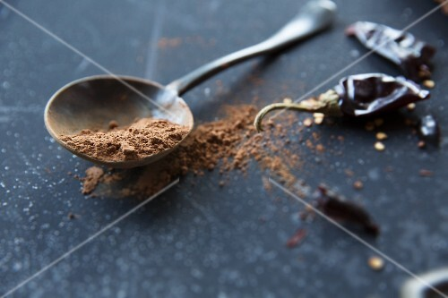 Cocoa powder on a spoon next to dried chilli peppers