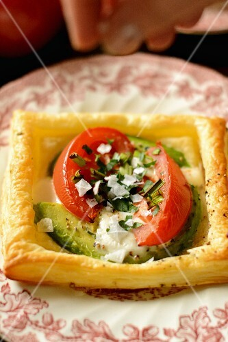 A puff pastry with baked egg, avocado and tomatoes being sprinkled with salt