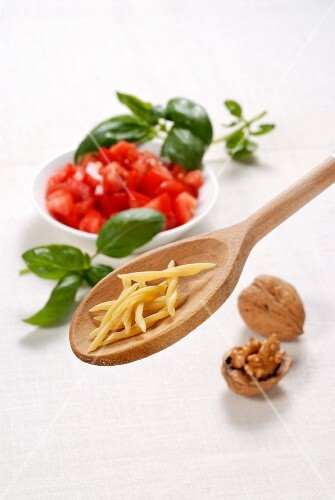 Strozzapreti on a wooden spoon with tomatoes, basil and walnuts