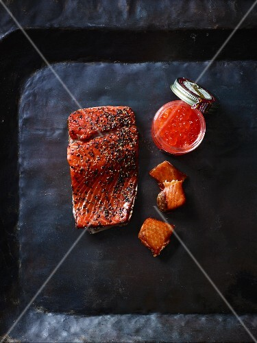 Smoked salmon and salmon caviar on a black tray