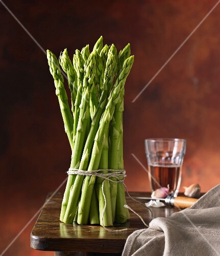 A bundle of green asparagus on a wooden table with wine and garlic