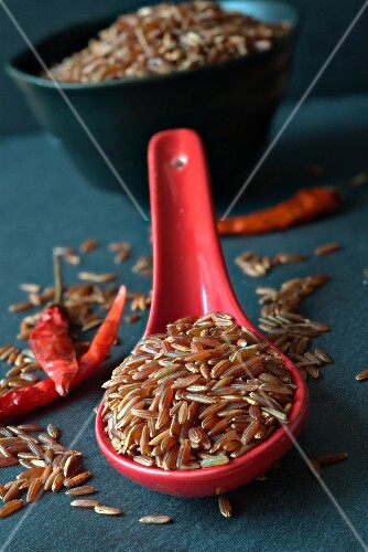 Red rice on a ceramic spoon and chilli peppers on a slate surface