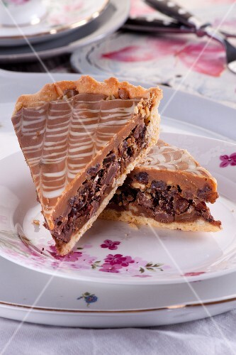 A slice of tart with dried figs, raisins, almonds and walnuts