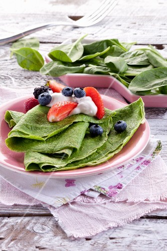 Spinach pancakes with berries and cream